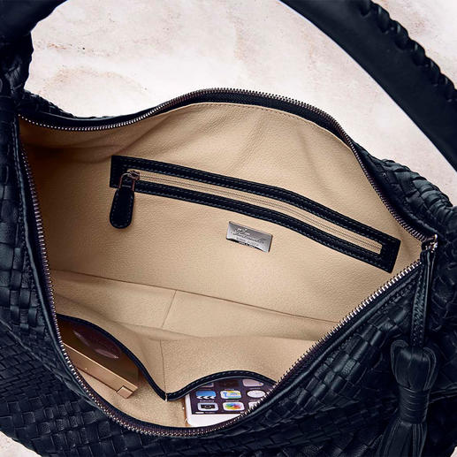 Two slot pockets and a separate zip pocket keep the contents organized and easily visible due to the light beige-coloured lining.